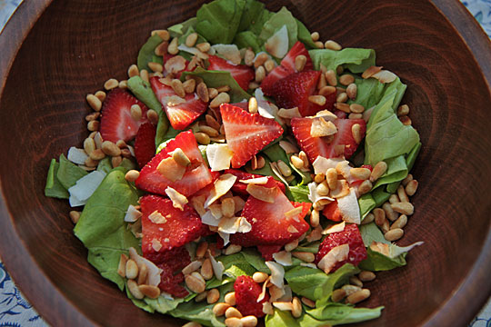 Salad with fresh strawberries, toasted coconut and pine nuts