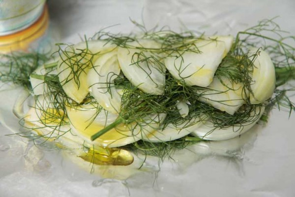 Layered onion slices, fennel fronds, and olive oil ready for the grill
