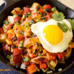 A skillet dish with potatoes, vegetables, chile, cheese and an egg