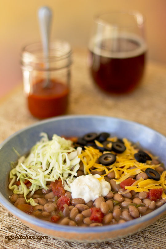 A bowl of pinto beans with an assortment of toppings