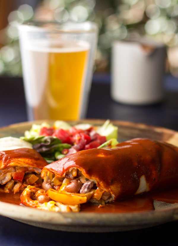 A vegetarian burrito with pinto beans and seared peppers and onions, smothered in New Mexico red chile sauce | mjskitchen.com